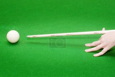 Hand ready to strike white pool ball
