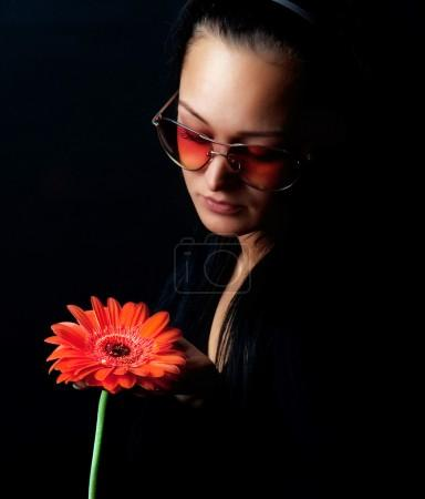 Cute woman holding a red flower