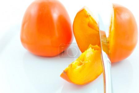 Two ripe persimmons and steel knife