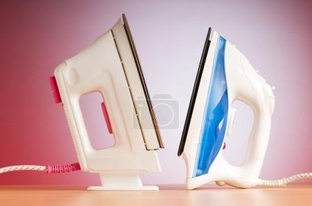 Modern electric iron against the colorful background