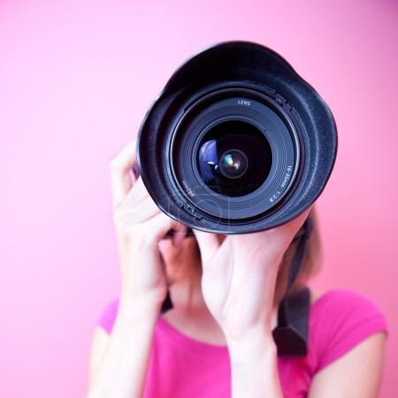 Female photographer pointing her super wide lens at you (color t