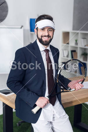 portrait of cheerful businessman with tennis equipment in office
