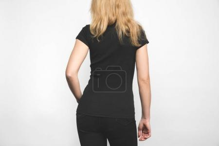 back view of young woman in blank black t-shirt on white