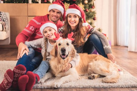 happy family in santa hats with dog in deer horns sitting near christmas tree