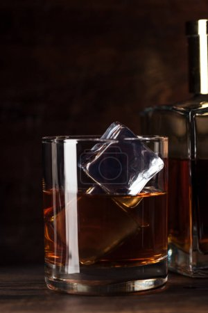 close-up view of glass of bourbon with ice cubes and bottle on wooden table