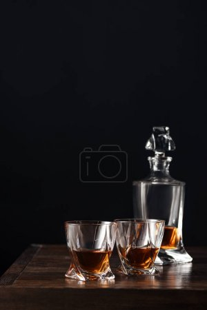 glasses and bottle of whisky on dark wooden table isolated on black