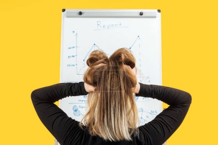 back view of businesswoman standing near white flipchart, holding hand on head