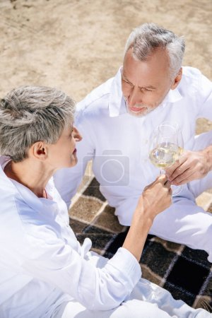 overhead view of senior couple sitting on blanket and clinking wine glasses with wine at beach