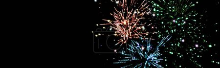 panoramic shot of blue, green and orange festive fireworks in dark night sky, isolated on black